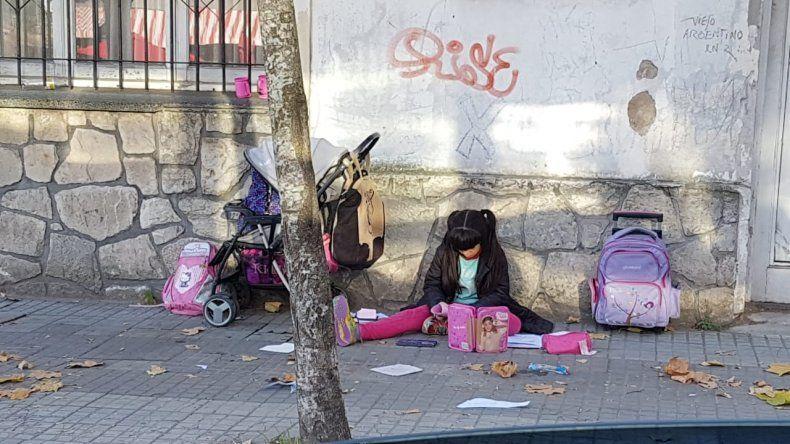 La imagen de la nena que hace la tarea en la calle